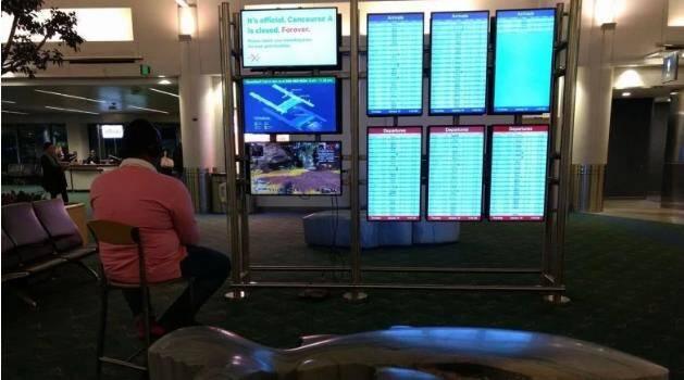 Havalimanındaki Ekranda PS4 Oynayan Adam
